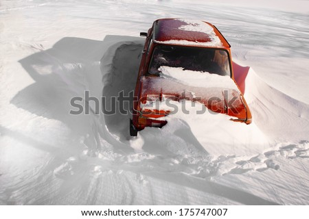 Snowbound red car by a bright day