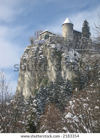 Snowcapped medieval castle standing over a precipice and overlooking a beautiful frozen lake.