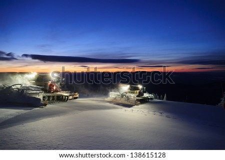 Snowcat grooming trails in the early morning in Stowe, Vermont, USA - stock photo