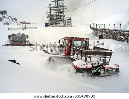 Snowcat in motion in snowfall on slope in the mountains at skiing resort Elbrus, preparing and clearing the track - stock photo