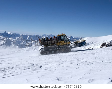 Snowcat with people going up the hill. The beautiful landscape of the Caucasus Mountains at Elbrus