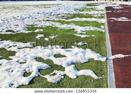 snowdrifts on outdoor soccer field in spring low season - stock photo