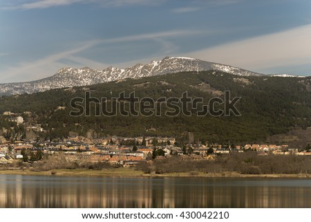 Snowed mountains. At bottom Navacerrada village, locate in north of Madrid community, Spain.