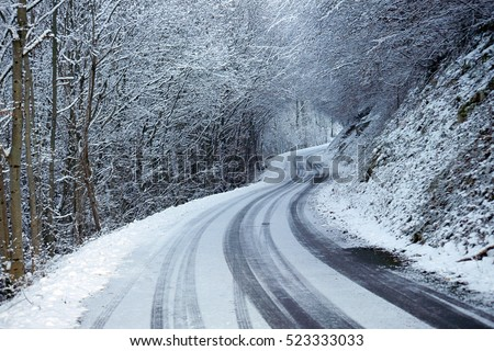 Snowed road and car tracks in winter in Savoy, France