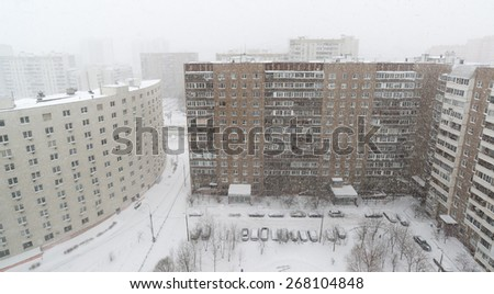 Snowfall on a residential building facade background. Winter mood