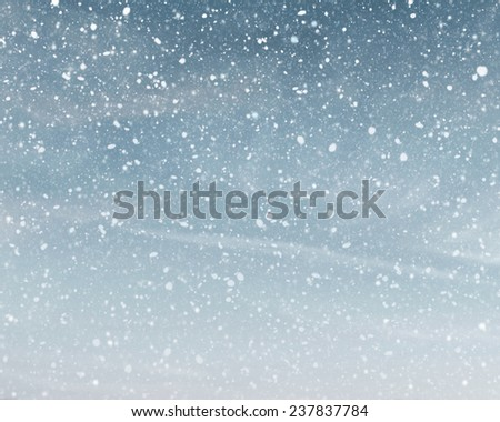 Snowfall on cloudy blue sky - stock photo