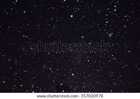 Snowfall on night black sky ideal for use as a texture layer in your project. - stock photo