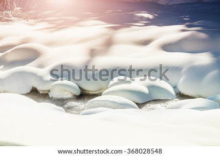 Snowfall on the river in winter forest. Beautiful winter landscape. - stock photo