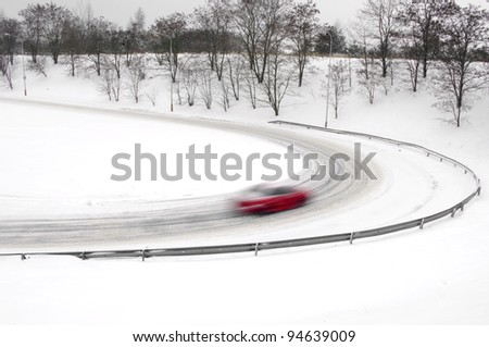 snowfall on the road, slippery way with car - stock photo