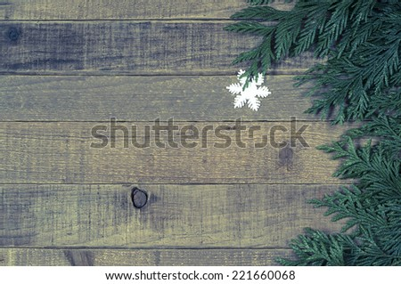 Snowflake Christmas Ornament with tree greens on side of rustic, old worn wood board background with room or space for copy, text, words.  Horizontal above view vintage, instagram retro treatment - stock photo