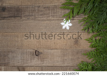 Snowflake Christmas Ornament with tree greens on side of rustic, old worn wood board background with room or space for copy, text, words.  Horizontal above view  - stock photo
