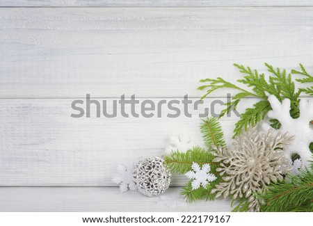 Snowflake Christmas Ornaments with fir greens against Rustic White Board Background with empty Room or space for copy, text, words.  Horizontal
