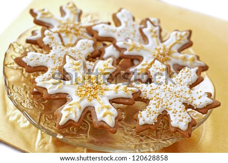 Snowflake gingerbread cookies decorated with icing, gold, and pearls. - stock photo
