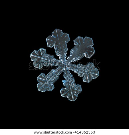 Snowflake isolated on black background: macro photo of real snow crystal, captured on dark woolen fabric in natural light. This is large snowflake of split plate type with simple shape.