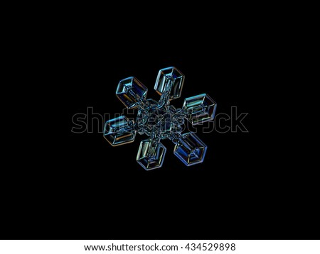 Snowflake isolated on black background: macro photo of real snow crystal, captured on glass surface with LED back light. This is medium size snowflake, resembling duck feet, or gecko's paw. - stock photo