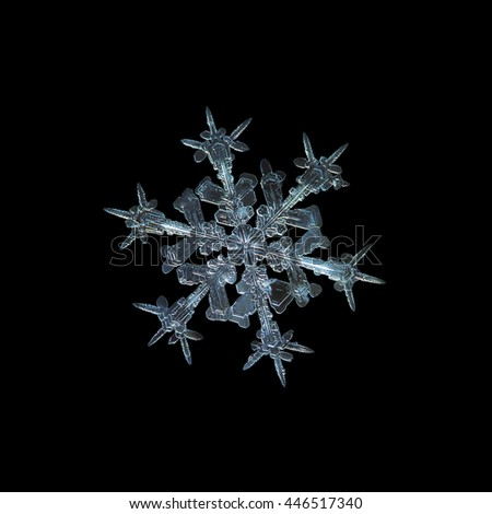 Snowflake isolated on black background: macro photo of real snow crystal, captured on glass with LED back light. This is medium size snowflake of stellar dendrite type with sharp, ornate arms. - stock photo