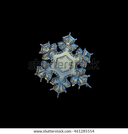 Snowflake isolated on black background. This is macro photo of real snow crystal with complex outer pattern and almost empty central hexagon, variant with yellow lighting.