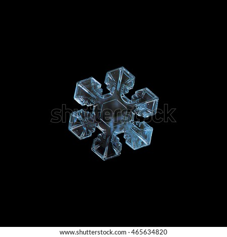 Snowflake isolated on black background. This is macro photo of real snow crystal with six short, broad arms and good symmetry.