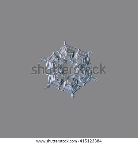 Snowflake isolated on light grey background: macro photo of real snow crystal, captured on glass surface with LED back light. This is medium size snowflake with amazing relief surface and symmetry. - stock photo