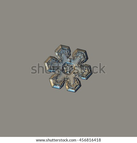 Snowflake isolated on uniform grey background. This is macro photo of real snow crystal with relief and glossy surface, variant with warm yellow lighting. - stock photo