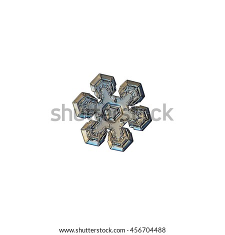 Snowflake isolated on white background. Closeup photograph of real snow crystal with interesting inner pattern and relief surface, variant with warm yellow lighting.