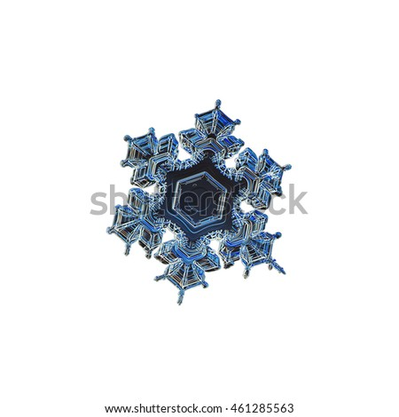 Snowflake isolated on white background. This is macro photo of real snow crystal with short arms and large central hexagon, variant in dark blue colors.