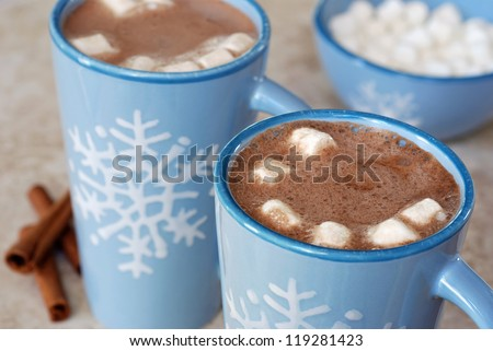 Snowflake mugs filled with hot chocolate and marshmallows on tile counter with cinnamon sticks along side.  Matching bowl with marshmallows in soft focus in background.  Closeup with shallow dof.