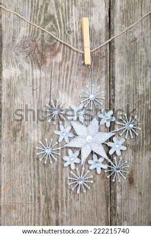 Snowflake on a rope on  wooden background. Winter holidays concept.