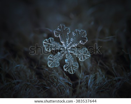 Snowflake on dark textured background: macro photo of real snow crystal on black woolen fabric in natural light. This is very large, but simple snowflake of with broad arms and tiny central hexagon.
