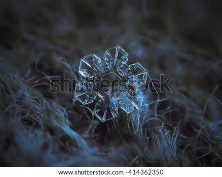 Snowflake on dark textured background: macro photo of real snow crystal on black woolen fabric in natural light. This is medium size snowflake with broad arms and symmetrical structure. - stock photo