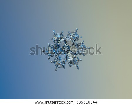 Snowflake on smooth gradient background: macro photo of real snow crystal on glass surface with LED back light. This is medium  size snowflake of stellar dendrite type. - stock photo