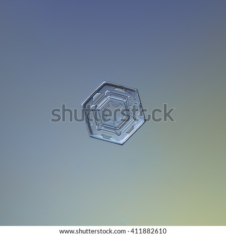 Snowflake on smooth gradient background: macro photo of real snow crystal on glass surface with LED back light. This is small hexagonal plate snowflake with symmetrical pattern inside. - stock photo