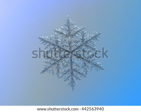 Snowflake on smooth gradient background: macro photo of real snow crystal on glass surface with LED back light. This is very large snowflake of fernlike dendrite type with complex structure of arms. - stock photo