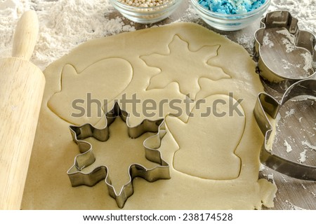 Snowflake, snowman and mitten cookie cutters cutting out holiday sugar cookies with wooden rolling pin and white dragees and blue snowflake candy sprinkles