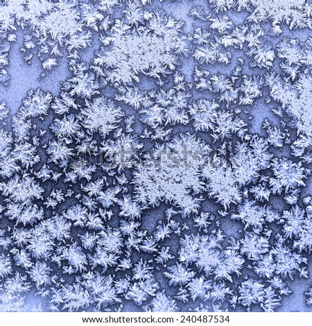 snowflakes and frost on frozen window in cold winter evening close up - stock photo