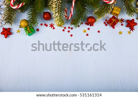 Snowflakes,candies, gifts and fir branches on a blue wooden table. Christmas decorations closeup.