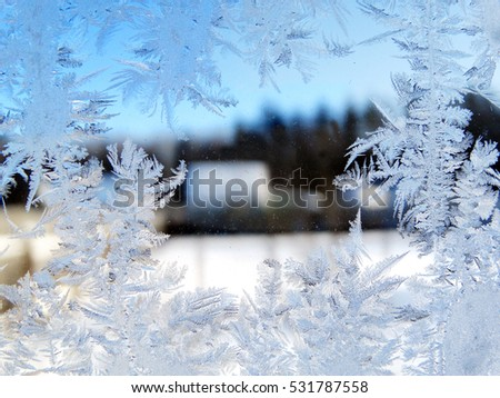 snowflakes ice pattern with sunlight on winter window galass