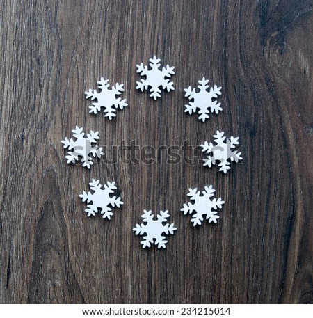 Snowflakes on the wooden background. - stock photo