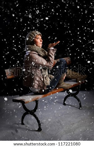 snowing on a woman seated on a bench at night - stock photo
