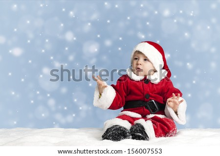 snowing on little child in santa clothes, seated in the snow