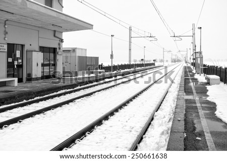 Snowing panorama with a train station, in the countryside region of Lomellina (between Lombardy and Piedmont, Northern Italy). Black and white photo - stock photo