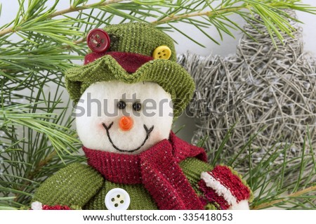 Snowman among fir branches with snow flakes. Winter