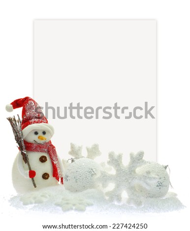 Snowman and Christmas ornaments in front of a paper card - stock photo