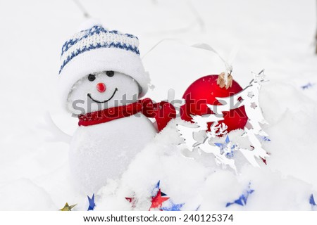 Snowman and multicolored star confetti and Christmas balls in the snow  - stock photo