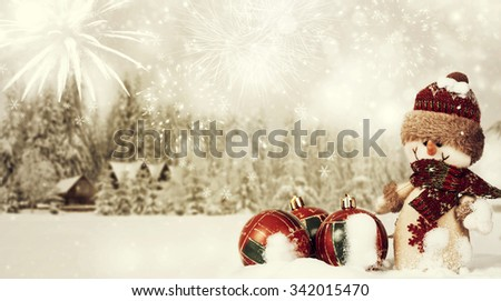 Snowman and red Christmas decorations in the snow, snow cowered pine trees in the background - stock photo