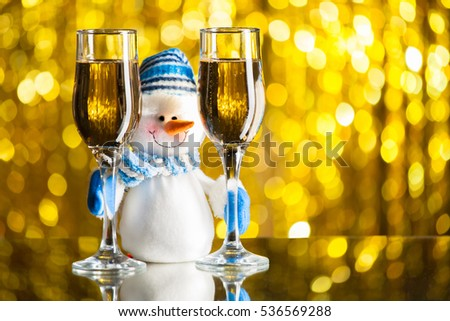 Snowman between glasses of champagne. Golden bokeh
