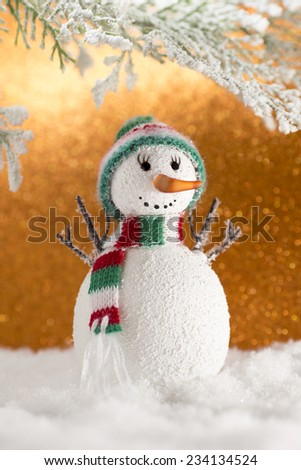 Snowman. Christmas symbol. Snowma with a hat and scarf in the snow.