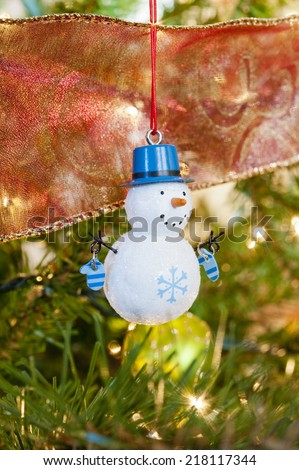 Snowman decoration hanging on a Christmas tree - stock photo