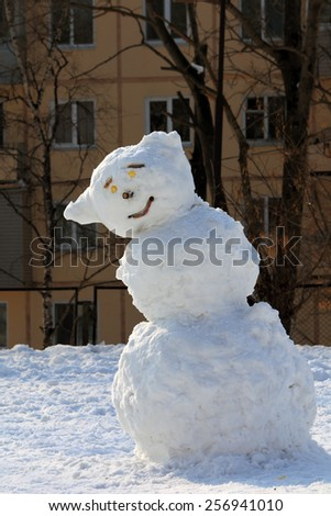 snowman fashioned children and adults on the playground near the house in winter - stock photo