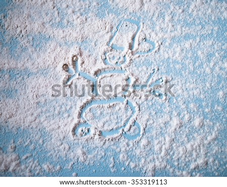 Snowman image of scattered flour on a blue table